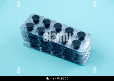 Activated carbon at blue background. packs of pills - Stock Photo