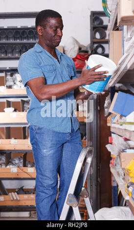 Focused African American man choosing supplies for home renovation in supermarket of building materials - Stock Photo
