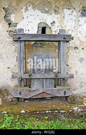 Old Antique wooden wine press in front of the rusty wall - Stock Photo