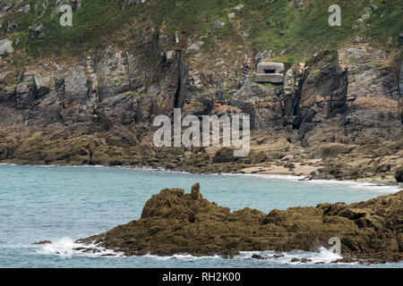 Coast near Saint-Malo (Brittany, France) with a german bunker from World War II, on a cloudy day in summer - Stock Photo