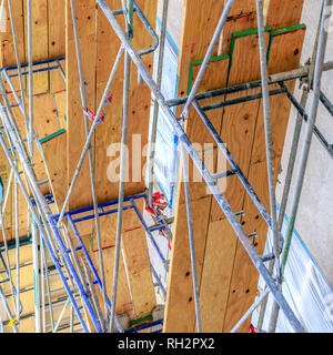 Scaffolding made of metal poles and wooden planks - Stock Photo