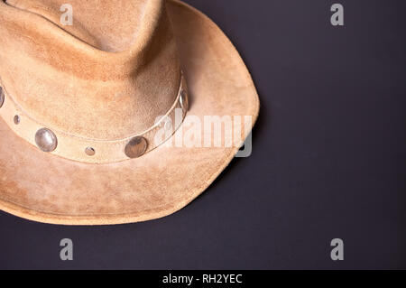 Brown cowboy hat on a black background - Stock Photo