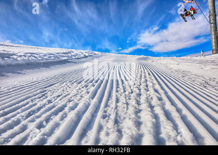 Empty ski path in the ski resort after passing truck and people on the ski chairs. Sunny day. Ski trail in Karakol, Kyrgyzstan. - Stock Photo