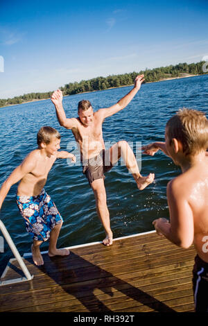 Father playing with sons at lake - Stock Photo