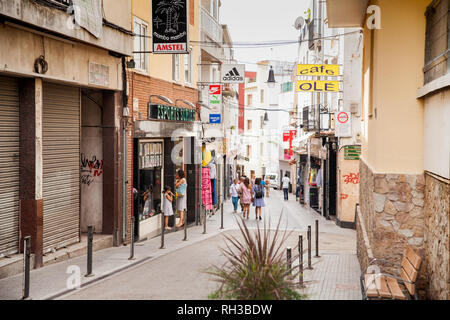 Shops and cafes near the narrow streets of Lloret de Mar. Downtown of Lloret, Spain. Tourists walking the streets of the city. - Stock Photo
