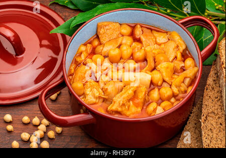 Chickpeas with tripe in clay pot. Aerial (top) view. On wooden background. - Stock Photo