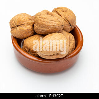 Walnuts in clay bowl (Various nuts collection). Isolated on white background. - Stock Photo