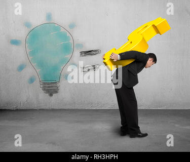 Man carrying gold money with glowing bulb drawing on wall - Stock Photo