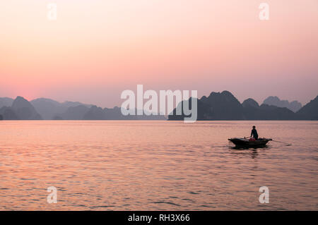 A Vietnamese woman rowing her wooden boat with limestone karst islands in background at sunset, Halong Bay, Vietnam - Stock Photo