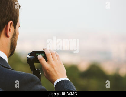 Business man in suit setting and using action camera on a stabilizer monopod gimbal - Stock Photo