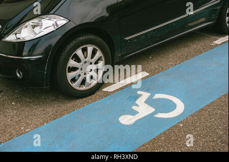 Car detail near dedicated blue stripe for disabled parking spaces with white pictogram painted on an asphalt - Stock Photo