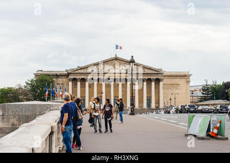 PARIS, FRANCE - MAY 21, 2016: Pedestrians on Pont de la Concorde with Assemblee Nationale The National Assembly in the background in central Paris - Stock Photo