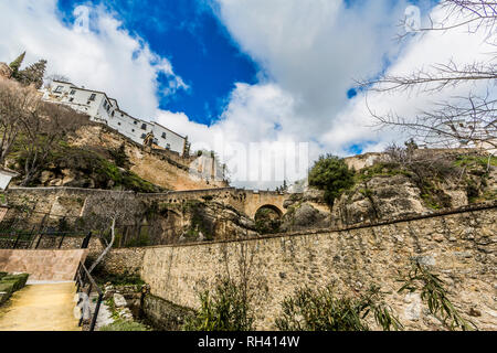 View from a lower perspective of a road with stone walls and the village of Ronda on the mountain, wonderful day with a blue sky and white clouds - Stock Photo