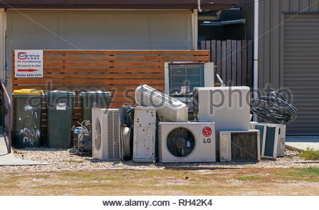 A pile of air-conditioners / a/c units, piled next to three wheelie bins on the footpath, outside Clarence Coast Air Conditioning business; in Yamba. - Stock Photo