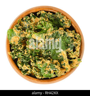 Homemade kale chips in wooden bowl. Dehydrated green leaf cabbage, coated with blended spices, nuts and vegetables. Snack and potato chip substitute. - Stock Photo