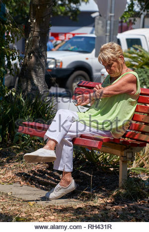 An older woman sitting on a red bench-seat, picking at her forearm in the sun and wearing pale green and white clothes and shoes; in Yamba, Australia. - Stock Photo