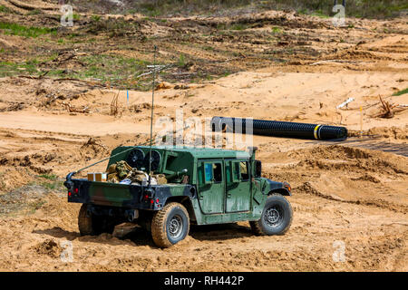 NATO Hummer military vehicles. Soldier on armored Hummer. International Military Training 'Saber Strike 2017', Adazi, Latvia, from 3 to 15 June 2017.  - Stock Photo