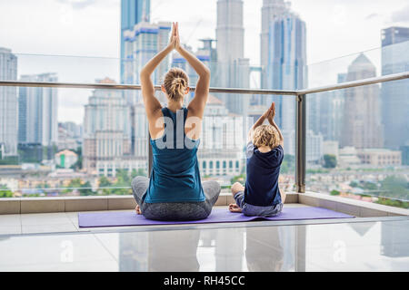 Mom and son are practicing yoga on the balcony in the background of a big city. Sports mom with kid doing morning work-out at home. Mum and child do - Stock Photo