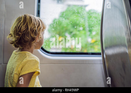 Beautiful toddler boy looking out train window outside, while it moving. Going on vacations and traveling by railway in summer - Stock Photo