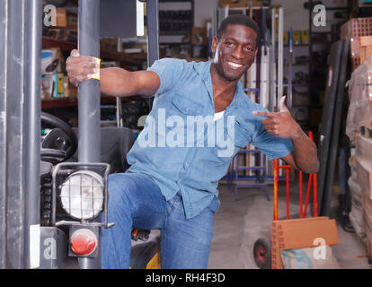 Adult African American worker on forklift in building materials store - Stock Photo