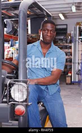 Focused African American worker driving forklift in building materials supermarket - Stock Photo