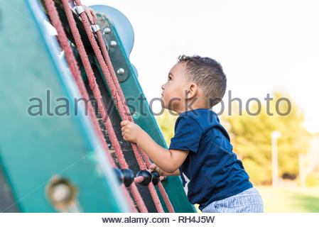 Child boy climbing a rope in the park and having fun outdoors. - Stock Photo