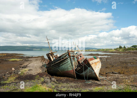 Two traditional painted wooden fishing boats on shore which are rotting away on Mull, ScotlandUK. - Stock Photo