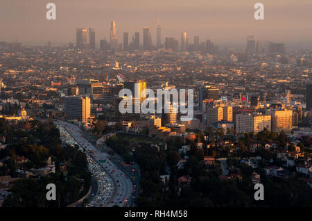 View of Hollywood with downtown Los Angeles in distance through smoggy skies at sunset. - Stock Photo