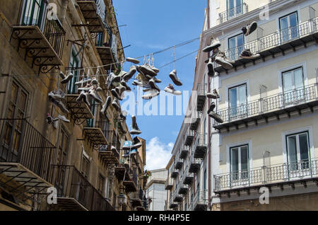 Trainers dangling from lines stretched across a street in the old town district of Palermo, Sicily. - Stock Photo