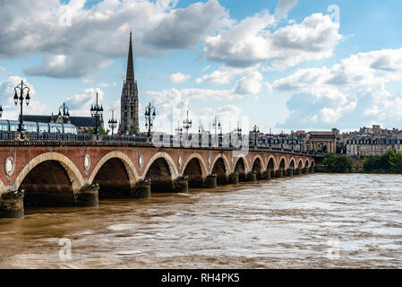 Pont de Pierre in Bordeuax against cityscape a sunny day of summer - Stock Photo