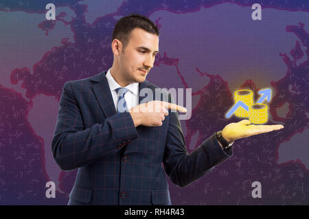 Broker man pointing with index finger to coins stack in palm as economic growth and profit concept on global map background - Stock Photo