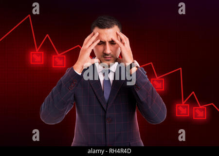 Worried broker facing economic crisis holding hands on temples because of headache caused by stress on background with red dropping graph - Stock Photo