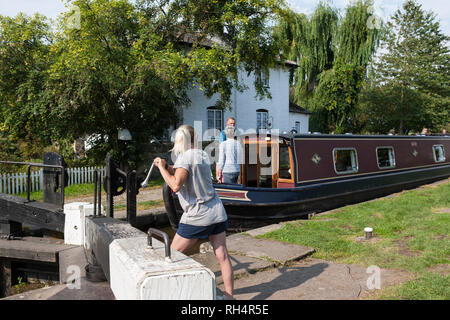 A girl operates the windlass for the ground paddles on New Marton Top Lock No.2, Llangollen Canal, Shropshire, England - Stock Photo