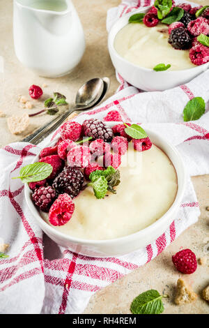 Two bowl with Semolina porridge with fresh berries, beige stone table copy space top view - Stock Photo