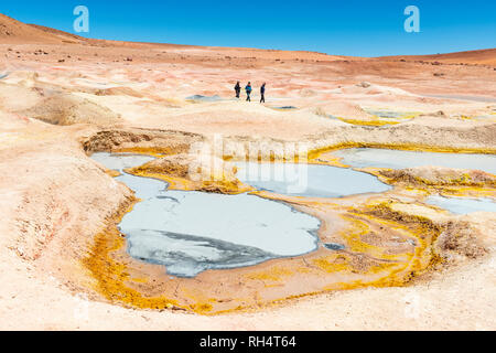 Three tourists walking by the mud pits, fumaroles and geysers of Sol de Manana near the Uyuni salt flat (Salar de Uyuni) in the altiplano of Bolivia. - Stock Photo