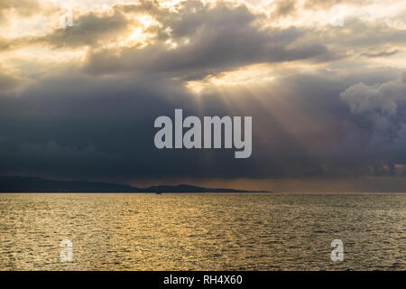 Scenic landscape ocean mountain silhouette view of sun rays bursting through clouds. Concept of breakthrough, hope, signs. - Stock Photo