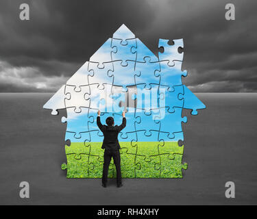 Businessman assembling house shape puzzles with nature image against cloudy sky - Stock Photo