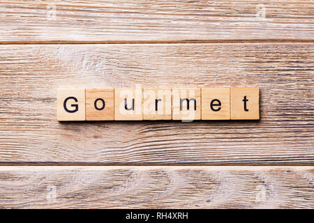 gourmet word written on wood block. gourmet text on wooden table for your desing, concept. - Stock Photo