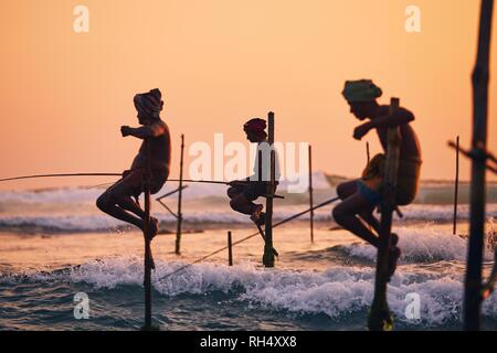 Silhouettes of the traditional fishermen. Traditional stilt fishing near Galle in Sri Lanka. - Stock Photo