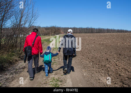 Kids hiking in the woods with sports hiking shoes. Father with children is walking along the path in boots and with backpacks. - Stock Photo