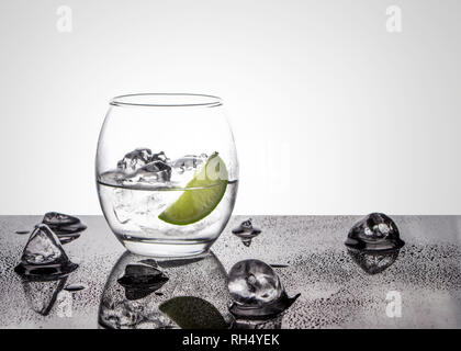 Vodka or Gin with lime in an oval glass on a glossy base with ice cubes against a white back lit background - Stock Photo