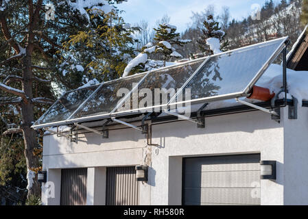 Solar hot water panels on a house roof. Electricity from the sun. House in the mountains. - Stock Photo