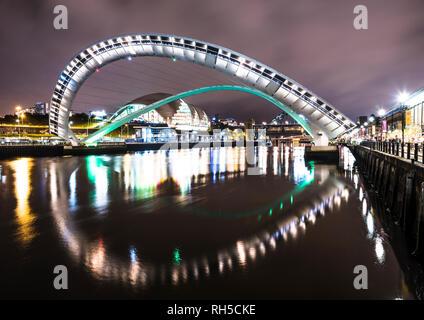 Night photo looking along the River Tyne towards Gateshead Millennium Bridge with Tyne Bridge in the background, Newcastle upon Tyne - Stock Photo
