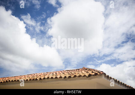 Cloudy blu skies creating negative space for copy over a typical terracotta tiled roof of a white house in Villa de Leyva, Colombia - Stock Photo