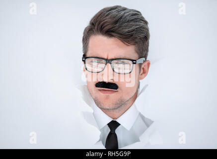 serious young businessman breaks through the paper - Stock Photo