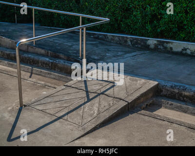 Old grunge wheelchair ramp with metal bar on green bush background. - Stock Photo
