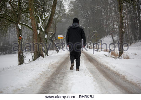 A man walking on a road on a cold and snowy winter's day in Franconia in Germany - Stock Photo