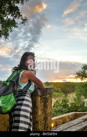 Travelling girl enjoying view to beautiful rural scenery after sunset. Happy woman looking at horizon in countryside. - Stock Photo