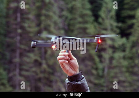 Filmmaker Scott Rulander retrieves a DJI Mavic Pro drone after a videography session in the Purcell Mountains of northwest Montana. - Stock Photo