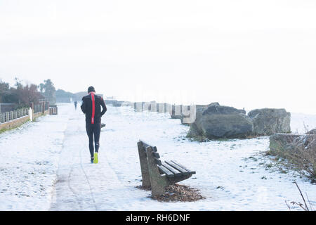 Ferring west Sussex, UK. Friday 1 st Febuary. UK weather. After moderate snowfall last night Ferring wakes to snow covered beaches and this runner braves the elements. Credit: Photovision Images News/Alamy Live News - Stock Photo